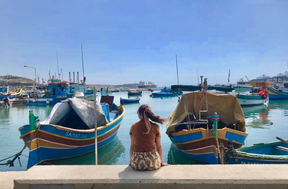Girl sitting by Marsaxlokk harbour watching the brightly painted fishing boats